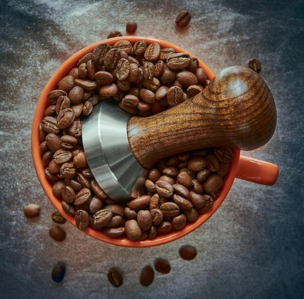 Manomissione del caffè in una tazza con chicchi di caffè su uno spazio d'argento