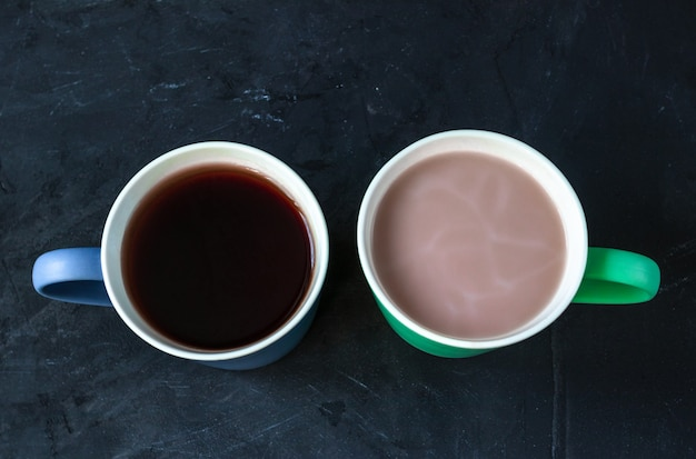 Caffè e tè nelle tazze sul fondo della lavagna posteriore. concetto di caffè vs tè