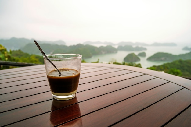 Caffè o tè sulle isole della tavola e sulle montagne. caffè vietnamita tradizionale in un bicchiere di vetro trasparente sullo sfondo di un bellissimo paesaggio della baia di halong nel nord del vietnam.