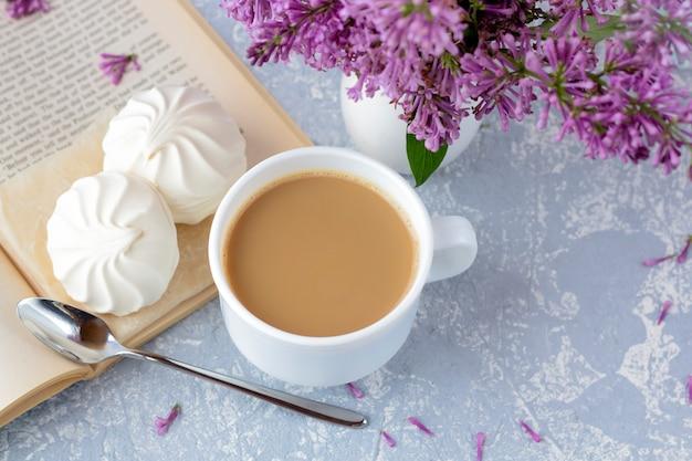 Caffè o tè con latte e caramelle gommosa e molle. leggendo un libro in giardino con una tazza di caffè. romantica natura morta con fiori lilla.