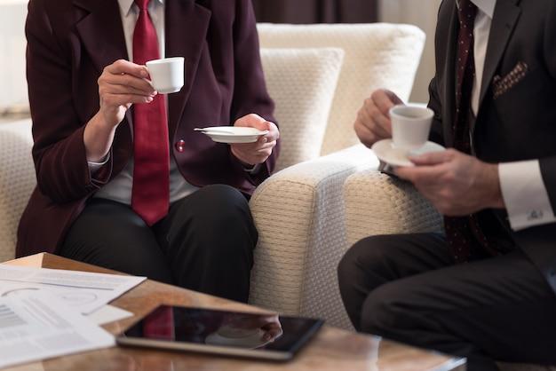 Tempo del caffè. bianco brillante belle tazze di caffè nelle mani di due uomini d'affari seduti in ufficio vicino al tavolo