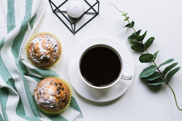 Caffè e due muffin sulla superficie bianca