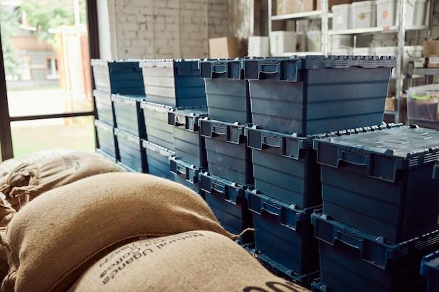 Magazzino del caffè con sacchi di tela e scatole di plastica blu con coperchi
