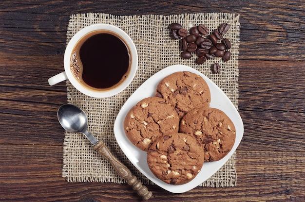 Caffè con biscotti al cioccolato sul tavolo di legno scuro dall'alto