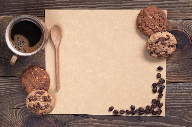 Caffè con biscotti al cioccolato e carta marrone vuota per il testo su sfondo di legno scuro, vista dall'alto