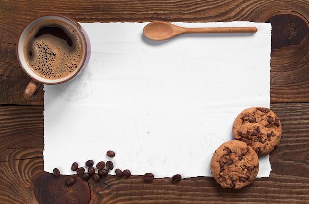 Caffè con biscotti al cioccolato e carta sporca vuota per il testo su sfondo di legno scuro, vista dall'alto