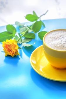 Caffè con latte di cocco e rosa gialla su fondo di legno blu