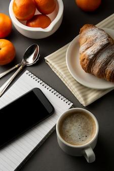 Caffè con croissant e agrumi. tavolo da lavoro con smart phone. pasticceria francese e tazza di caffè.