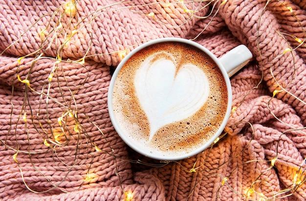 Caffè con un motivo a cuore su una calda superficie del maglione lavorato a maglia