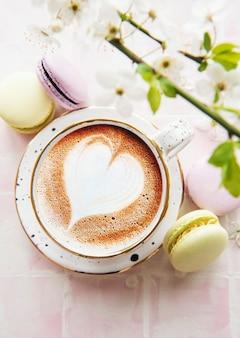 Caffè con un motivo a forma di cuore e dolci amaretti su uno sfondo di piastrelle rosa