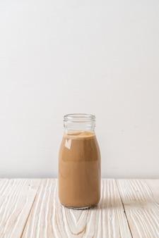 Caffè con latte in bottiglia sul tavolo di legno