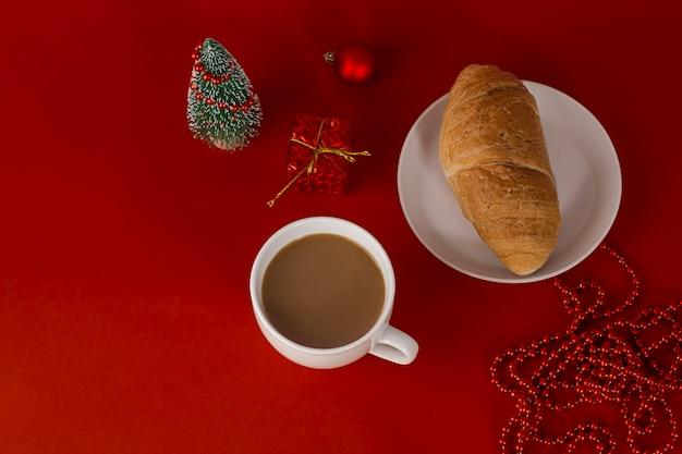 Caffè con latte e croissant su sfondo rosso con decorazioni natalizie