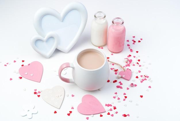 Caffè con latte in una tazza rotonda su uno sfondo romantico con una cornice bianca a forma di cuore
