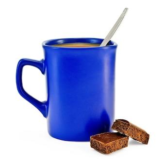 Caffè con latte, cucchiaio d'argento in tazza blu, fette di cioccolato marrone isolate