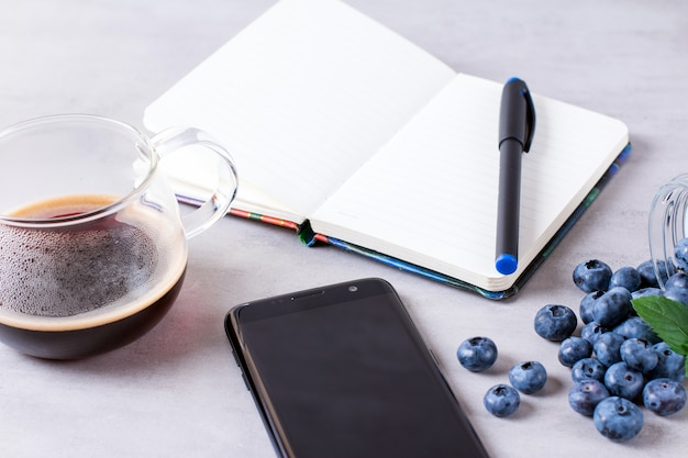 Caffè con taccuino e telefono