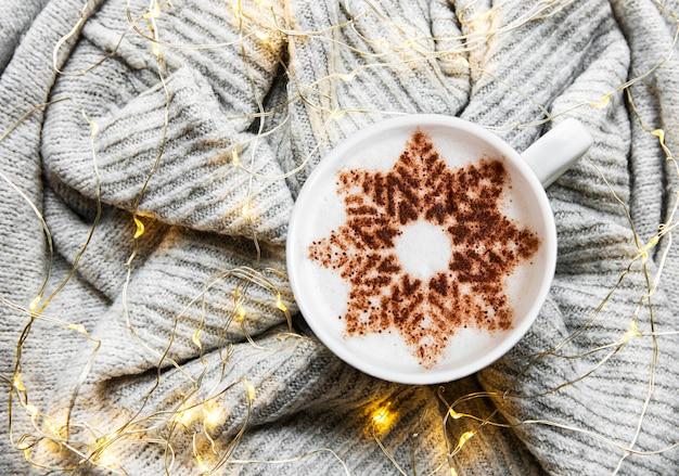 Caffè con un motivo a fiocco di neve su una calda superficie del maglione lavorato a maglia