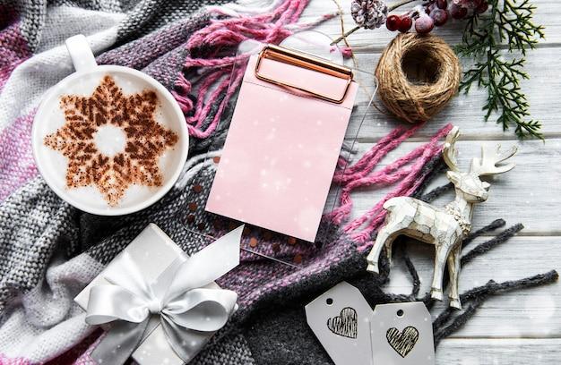 Caffè con motivo a fiocco di neve su una calda coperta di lana, decorazioni natalizie e un taccuino per i programmi per il prossimo anno