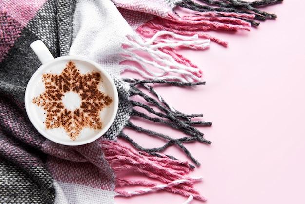 Caffè con un motivo a fiocco di neve su una calda superficie a quadri di lana