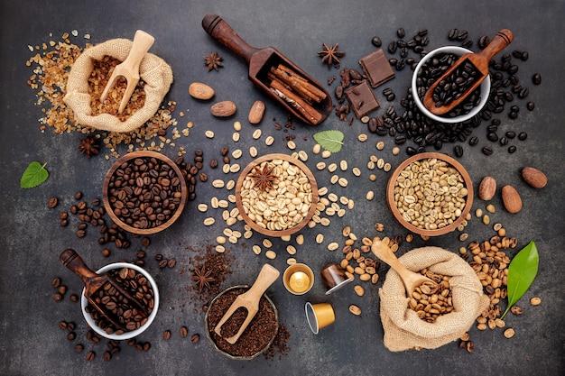 Caffè con vari chicchi di caffè tostati e ingredienti saporiti per preparare gustosi caffè su pietra scura.