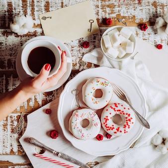 Caffè in mano a una donna e tre ciambelle con glassa bianca. san valentino