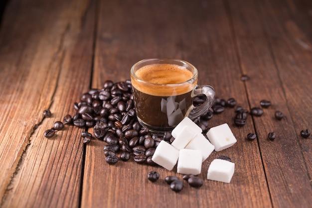 Caffè sui precedenti di legno, concetto del fondo del caffè.