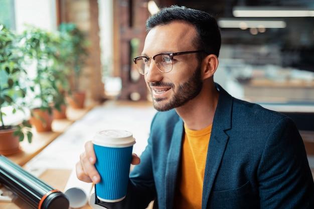 Caffè al lavoro. bell'uomo che indossa una giacca scura che beve caffè al lavoro prima di iniziare il progetto