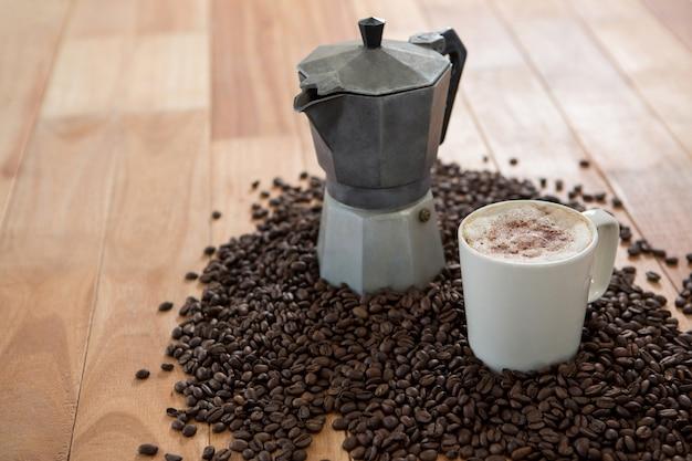 Macchina per il caffè con chicchi di caffè e tazza di caffè