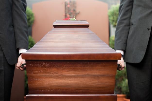 Portatore di bara che trasporta scrigno al funerale