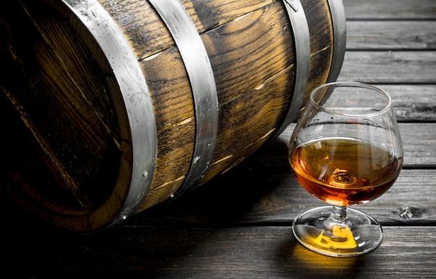 Cognac in un bicchiere con una botte. su legno