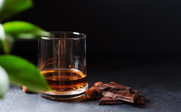 Cognac o whisky o brandy in un bicchiere. pezzi di cioccolato e nocciole.
