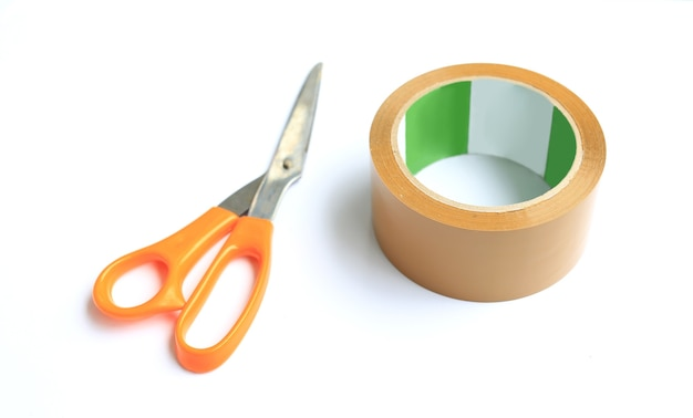 Nastro adesivo e forbici della bobina isolati sopra fondo bianco. attrezzatura universale per l'imballaggio. messa a fuoco selettiva