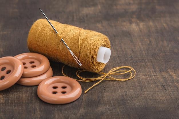 La bobina è filo giallo e pulsanti sul tavolo di legno.