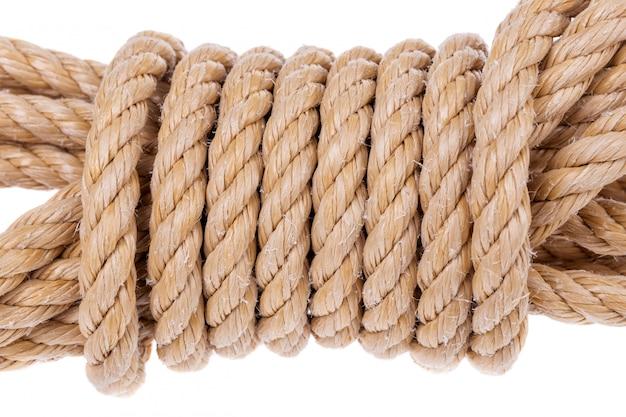 Bobina di corda attorcigliata in un rotolo. su un muro bianco