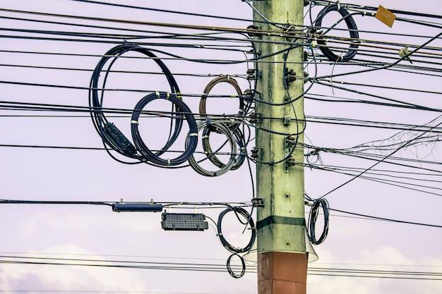 Bobine del cavo di elettricità sul palo di elettricità sulle nuvole del cielo blu