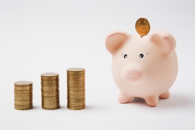 Moneta che cade nel salvadanaio rosa, pile di monete d'oro isolate su sfondo bianco. accumulo di denaro investment banking o concetto di ricchezza di servizi alle imprese. copia spazio pubblicitario mock up.