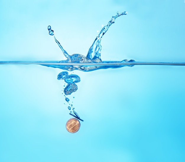 Moneta che spruzza nell'acqua come simbolo di valuta instabile. denaro, economia, crisi, concetto di globalizzazione.