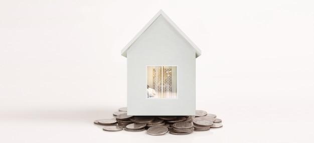 Piani di risparmio del modello di casa con pila di monete per il concetto di alloggio, casa e immobiliare
