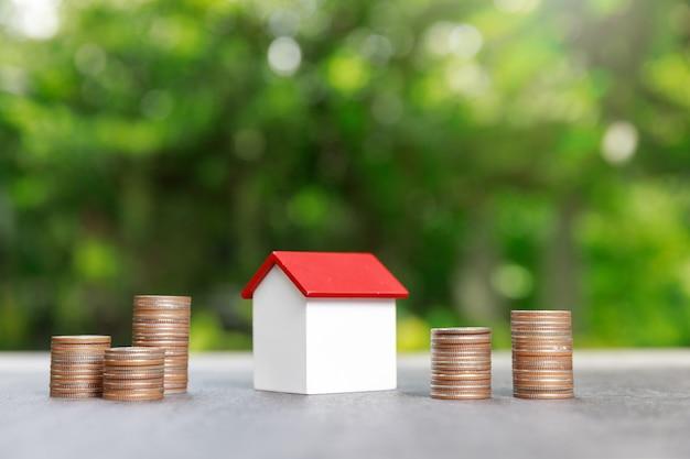 Pila della moneta con il modello della casa su verde.