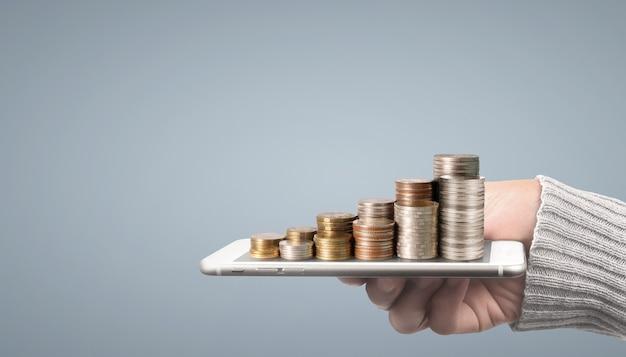 Moneta e concetto di ricchezza. un sacco di soldi su un vetro che rappresenta una tavoletta digitale