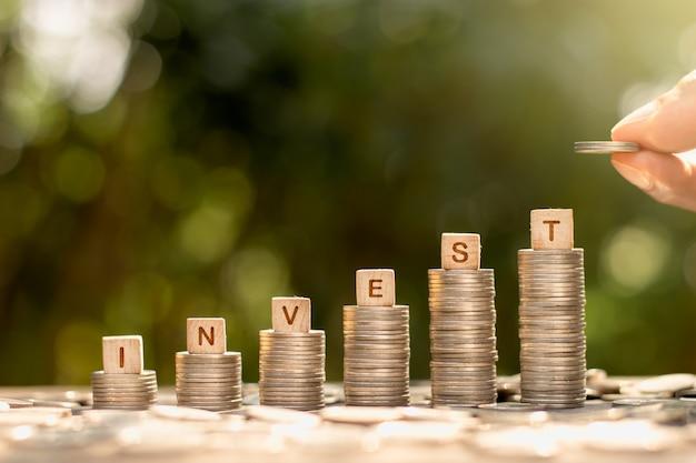 Le monete sono impilate, molte cose e le mani di un uomo stanno raccogliendo le monete, pensando di investire denaro.