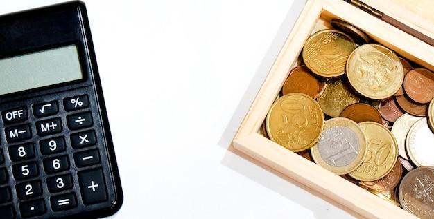 Monete e calcolatrice, quantità diverse, copia spazio, su sfondo bianco