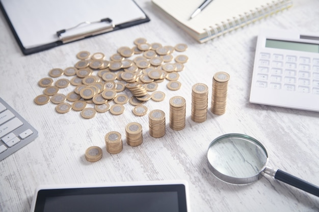 Monete, calcolatrice e altri oggetti sulla scrivania.
