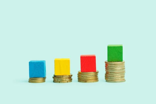 Monete e blocchi di legno colorati come barre infografica su sfondo blu