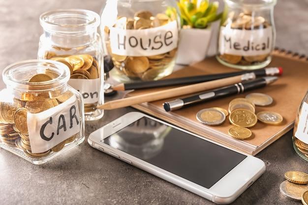 Monete per diverse esigenze in barattoli di vetro sul tavolo