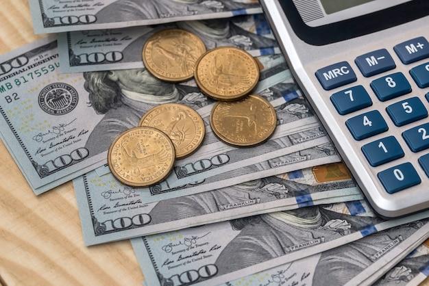 Monete, banconote da un dollaro e calcolatrice