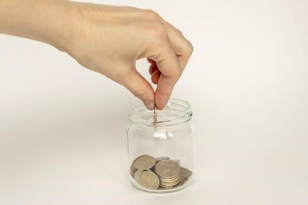 Monete che cadono in un barattolo di vetro