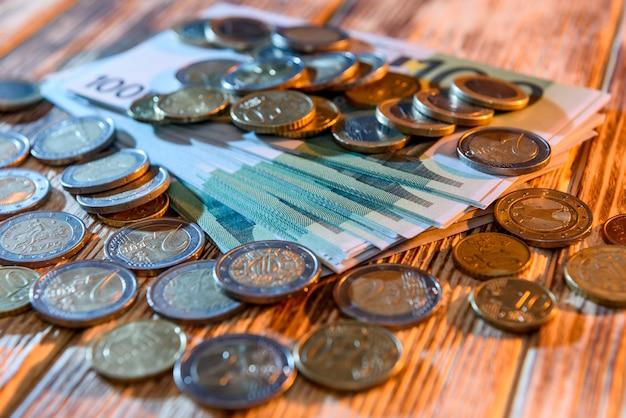 Monete sulle banconote in euro alla scrivania in legno