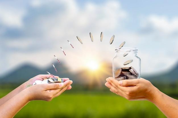 Le monete galleggiano di mano in bottiglia per risparmiare denaro nelle mani dell'uomo. idee per risparmiare e affari di successo