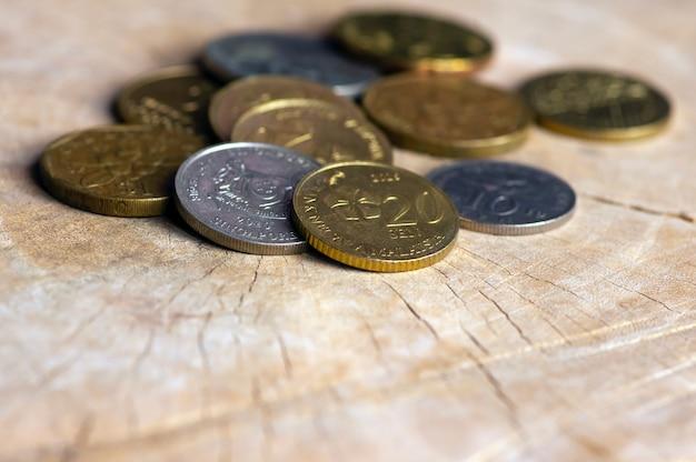 Monete provenienti da paesi asiatici, su un vecchio tavolo di legno, messa a fuoco selezionata
