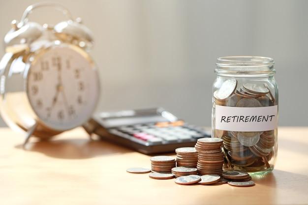 Monete in barattolo di vetro con calcolatrice e sveglia per risparmiare tempo per il concetto di pensione, pianificazione della pensione.